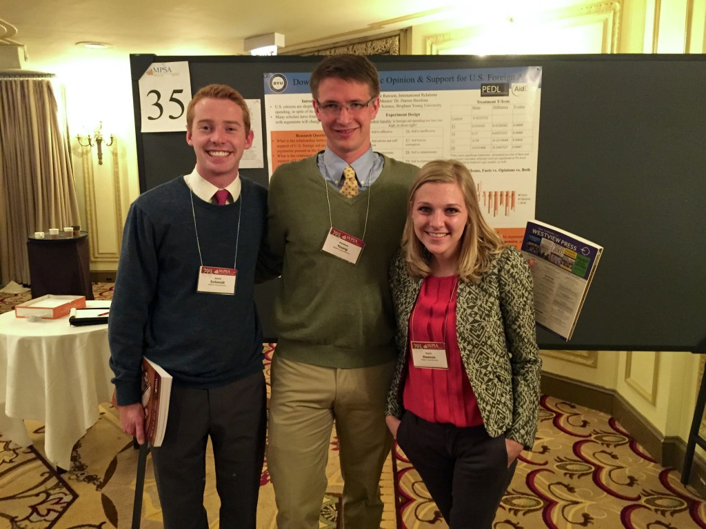 Political science students Soren Schmidt and Matthew Young along with international relations student Taylor Rawson stand at their booth at the 2015 Midwest Political Science Association (MPSA).