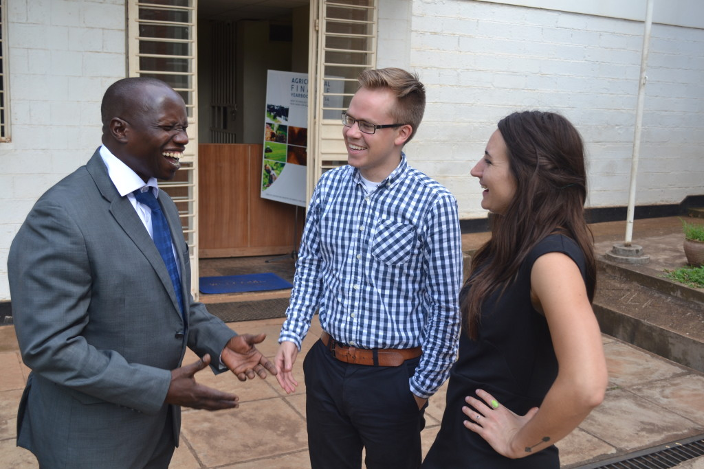 Robert Francis (center) talking with his supervisor, Dr. Alex Ijjo (left) and AidData colleague, Emily (right). The three worked together at the Economic Policy Research Center in Kampala.